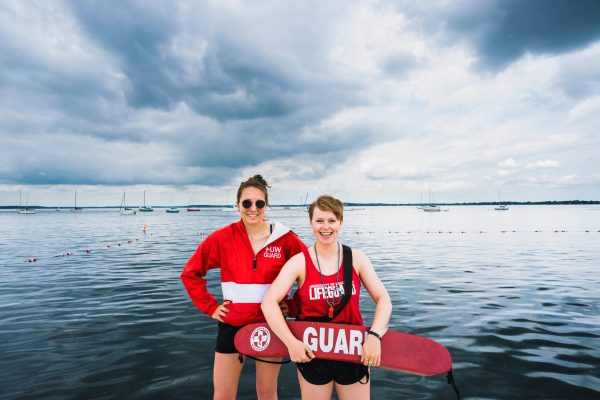 lifeguards smiling in their lifeguard suits, cloudy day on lake mendota