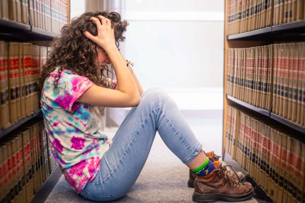 stressed person sitting between book stacks, tie dye shirt, head in hands