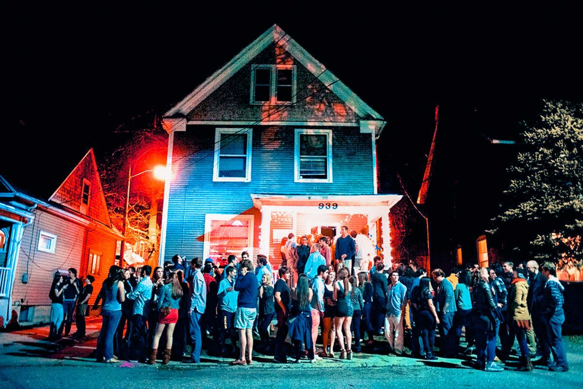 nighttime shot of people setanding outside an old house during a house party