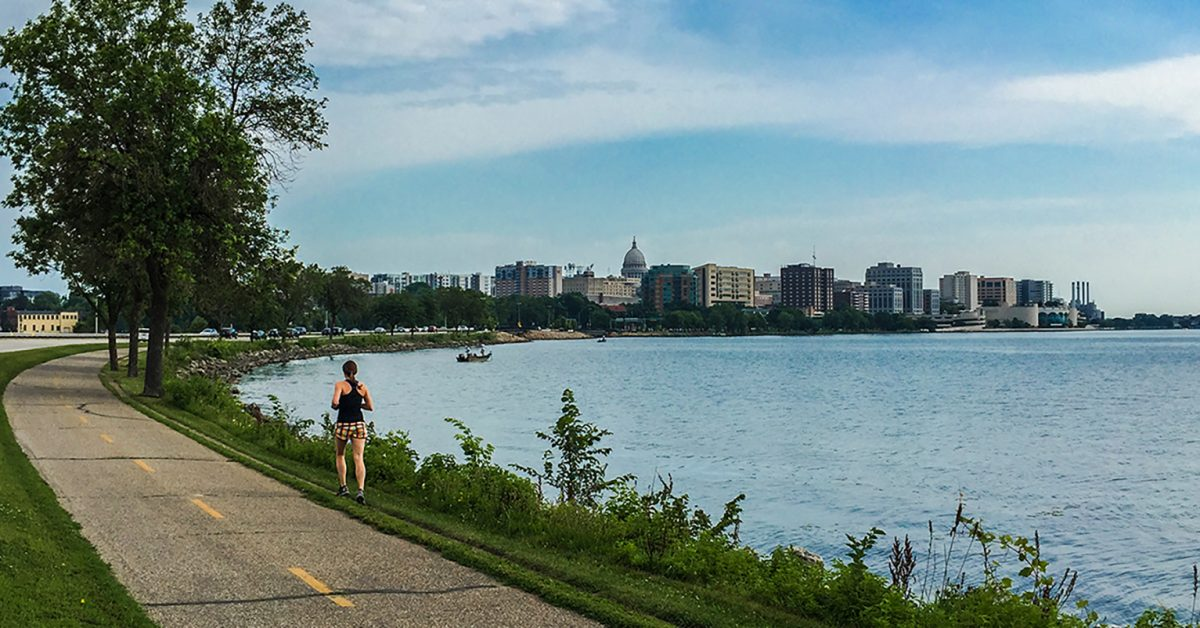 shoreline of madison showing lake monona and a runner on the side of the bikepath, capital in the background