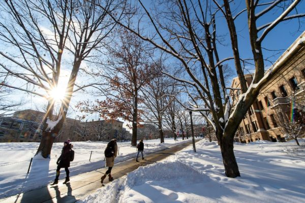 Students walk along the sidewalks leading to and from Bascom Hill on a snowy day.