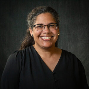 Leya Moore pictured smiling, wearing glasses and a black shirt.