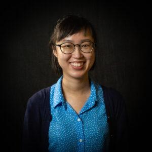 Sin U Lam wearing a blue shirt and black sweater
