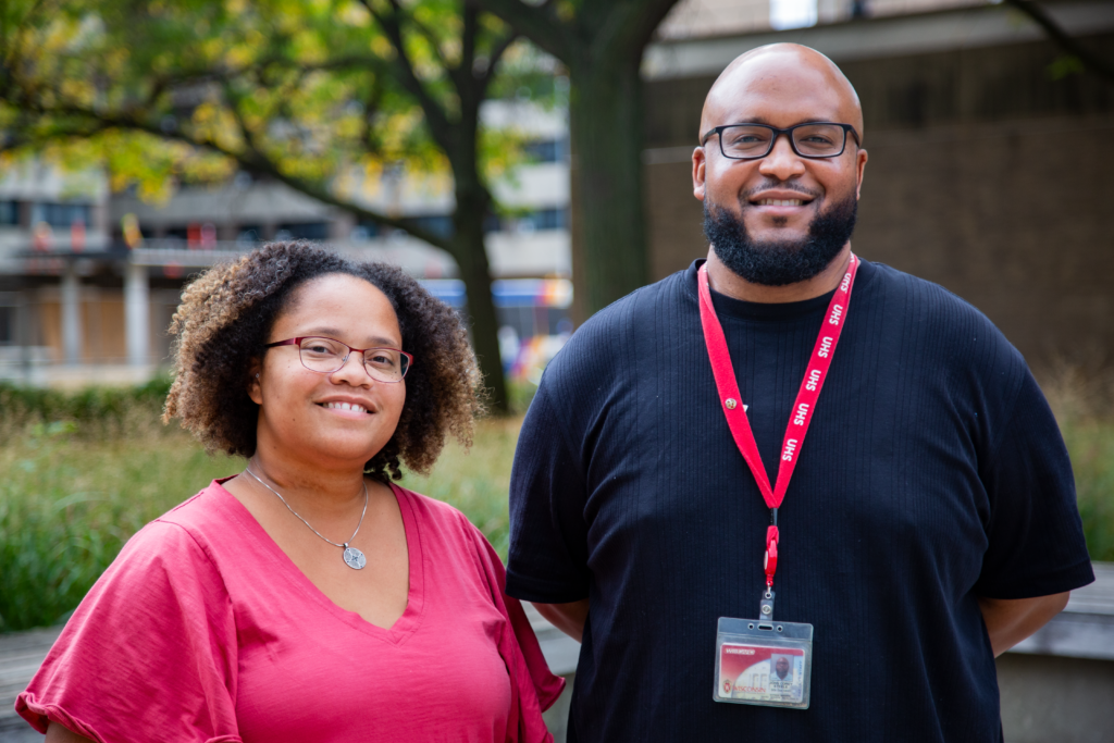 Josie Montañez-Tyler and Corey Steele, both UHS providers, are pictured outside with a tree in the background. Josie wears a red shirt and Corey wears a black shirt with a red UHS lanyard.