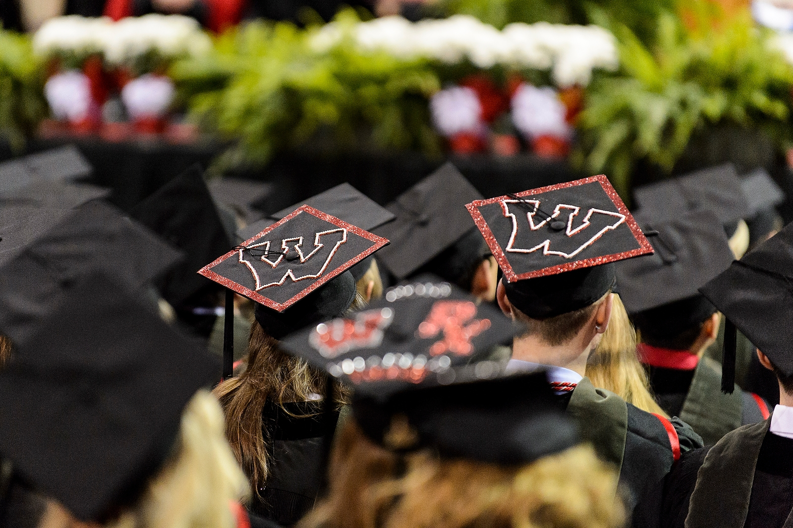 Students wearing graduation caps decorated with motion W's.