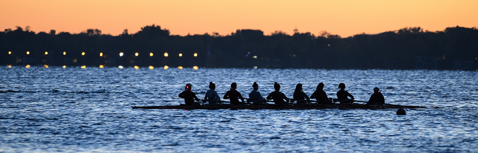 With nighttime giving way to dawn, the Wisconsin women's crew team rows along Lake Mendota near the University of Wisconsin-Madison campus during an autumn sunrise practice on Oct. 14, 2015. (Photo by Jeff Miller/UW-Madison)