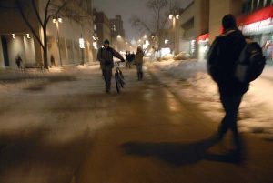 Image of students walking on Library Mall. It is nighttime and snowy.