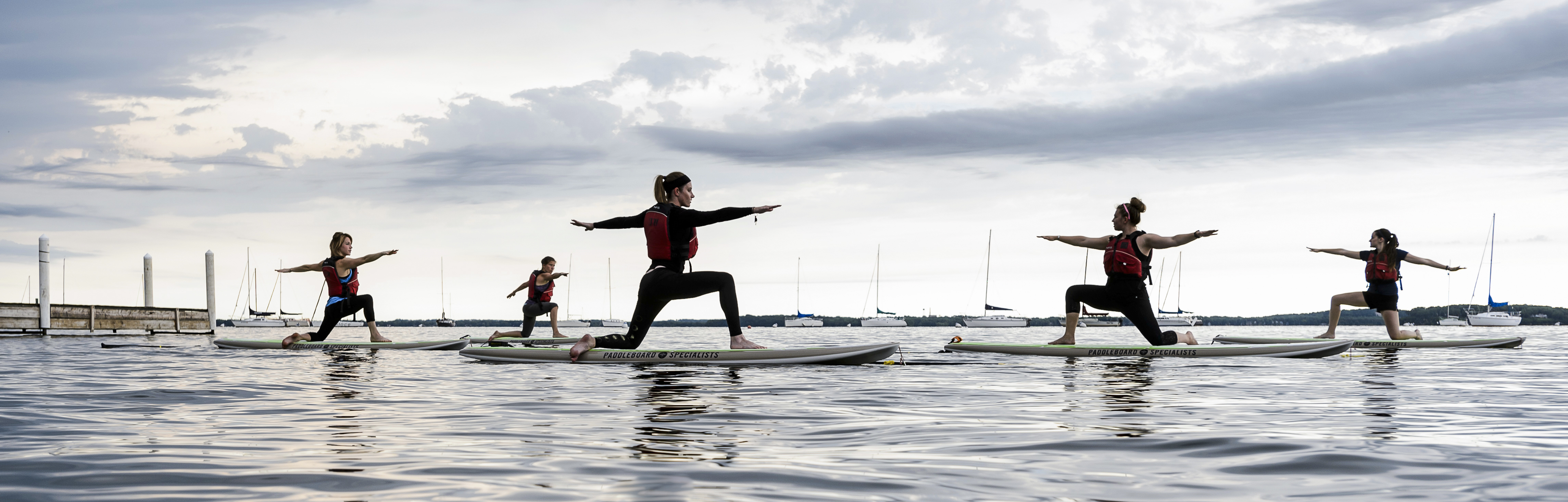 Undeterred by darkening morning skies and an approaching storm front, a group of women maintain balance during an Outdoor UW standup paddleboard (SUP) yoga class led by instructor Sarah Calvert, second from right, on Lake Mendota near the Memorial Union Terrace at the University of Wisconsin-Madison during spring on June 12, 2016. Outdoor UW is home to outdoor equipment rentals and the Wisconsin Hoofers. (Photo by Jeff Miller/UW-Madison)