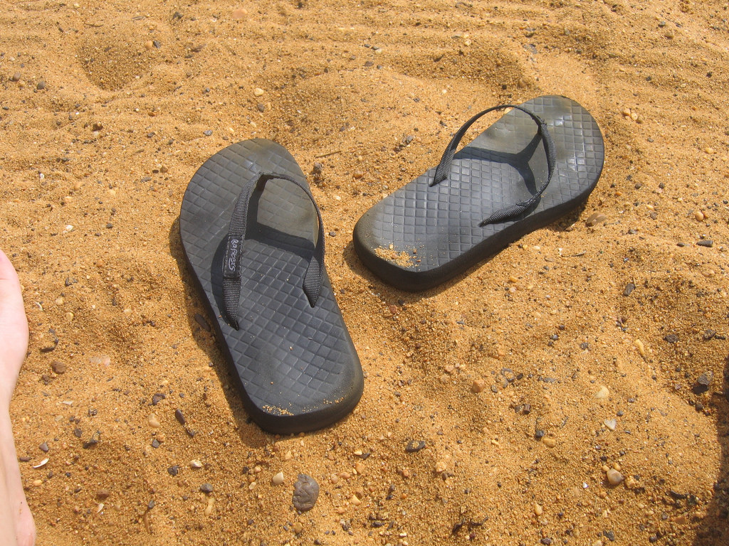 Image of flip flops in the sand.